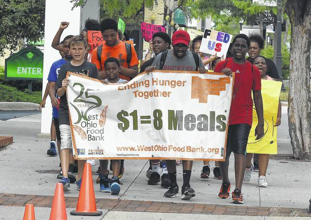 Leading a march to end hunger while holding a banner are Landen Paul, left, Jayden Davis, Daquan Knuckles and Zion Brown as the group crosses Market Street into Lima's Town Square. Lima Area Freedom Schools led a march to bring awareness to those who could miss meals due to potential budget cuts.