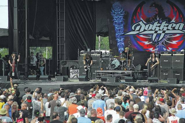 Dokken guitarist Jon Levin plays a blistering guitar riff as lead singer Don Dokken admires his work on the first day of Loud N Lima at the Allen County Fairgrounds Friday.