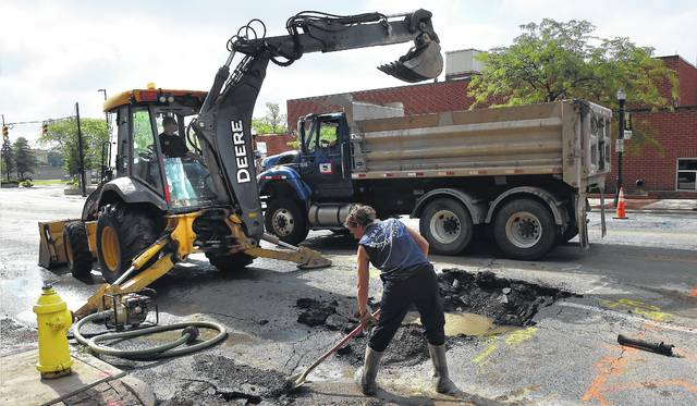 Water distribution employees for the city of Lima use a backhoe to repair an 8-inch waterline break between Elizabeth and Main streets in downtown Lima on Monday morning. The break occurred at 7 a.m. Monday.