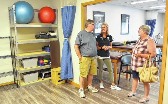 Physical therapist Maria Zenz, center, talks with Doug and Julie Weaver, of Elida, at an open house Tuesday evening in Northwest Physical Therapy's new office in Lima.