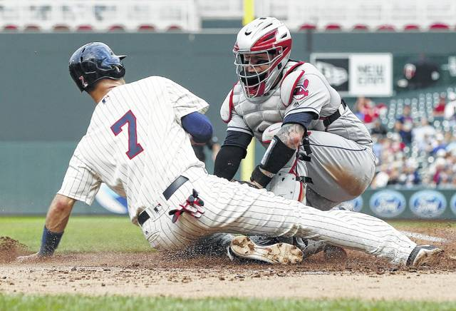 Minnesota's Joe Mauer is tagged out at the plate by Cleveland's Roberto Perez during the second game of a Thursday's doubleheader in Minneapolis.