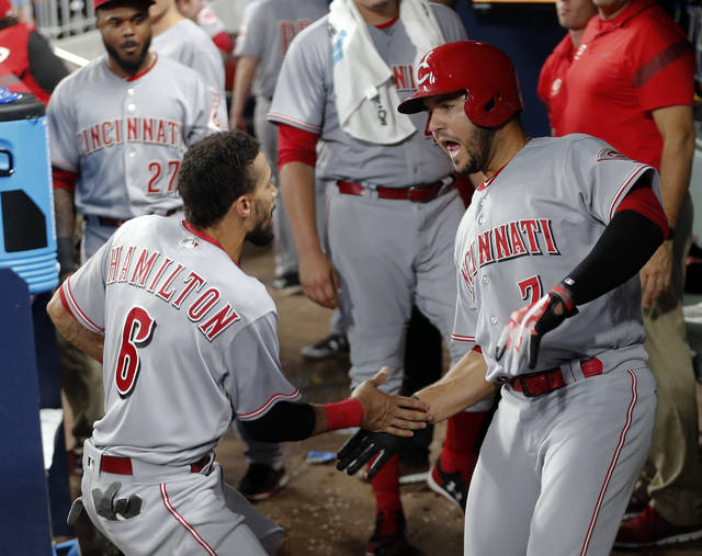 Cincinnati Reds' Eugenio Suarez (7) celebrates with Billy Hamilton (6) after hitting a home run during the sixth inning of a baseball game against the Atlanta Braves on Friday, Aug. 18, 2017, in Atlanta. (AP Photo/John Bazemore)