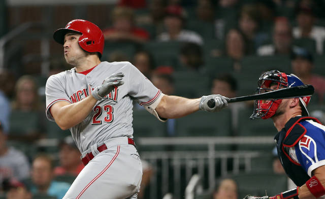 Cincinnati Reds' Adam Duvall (23) follows through on a two-run home run during the sixth inning of a baseball game against the Atlanta Braves on Friday, Aug. 18, 2017, in Atlanta. Braves catcher Tyler Flowers is at right. (AP Photo/John Bazemore)