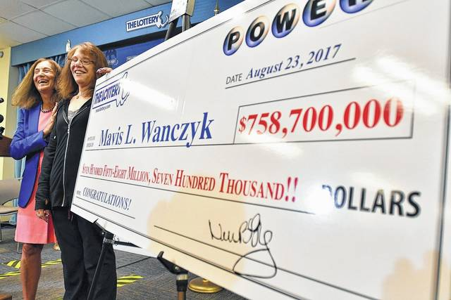 Mavis Wanczyk, of Chicopee, Mass., stands by a poster of her winnings during a news conference where she claimed the $758.7 million Powerball prize at Massachusetts State Lottery headquarters, Thursday, Aug. 24, 2017, in Braintree, Mass. Officials said it is the largest single-ticket Powerball prize in U.S. history. At left is state treasurer Deb Goldberg.