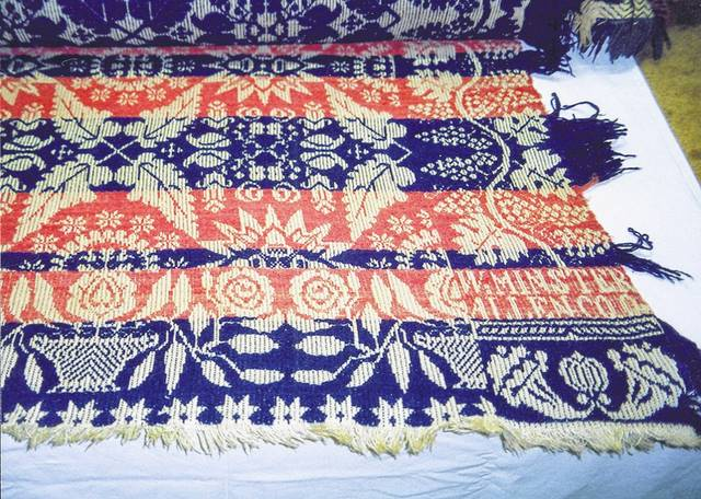 A summer-winter coverlet with grape/leaf border. The coverlet was woven in 1846 in Westminster, weaver unknown. It was donated to the Allen County Historical Society by Helen Basinger Reily.