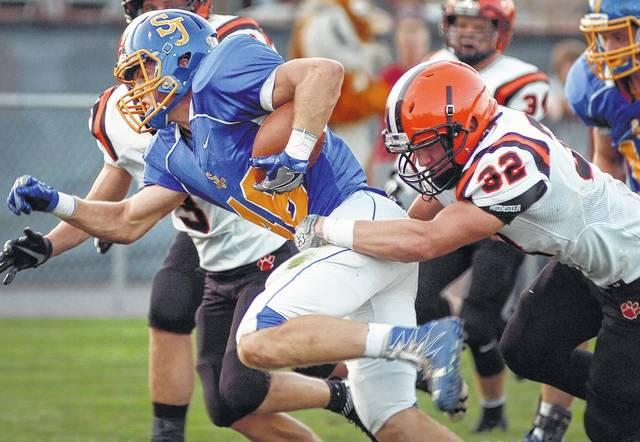 Delphos St. John's ball carrier Cole Reindel is tackled by Versailles' Kurtis Rutschilling during Saturday night's game at Stadium Park in Delphos. See more game photos at LimaScores.com.