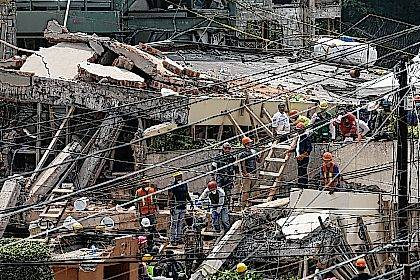 Search and rescue efforts continue at the Enrique Rebsamen school that collapsed after an earthquake in Mexico City, Wednesday, Sept. 20, 2017. Police, firefighters and ordinary Mexicans dug frantically through the rubble of collapsed schools, homes and apartment buildings early Wednesday, looking for survivors of Mexico's deadliest earthquake in decades as the number of confirmed fatalities climbs. One of the most desperate rescue efforts was at this school, where a wing of the three-story building collapsed Tuesday into a massive pancake of concrete slabs. (AP Photo/Marco Ugarte)