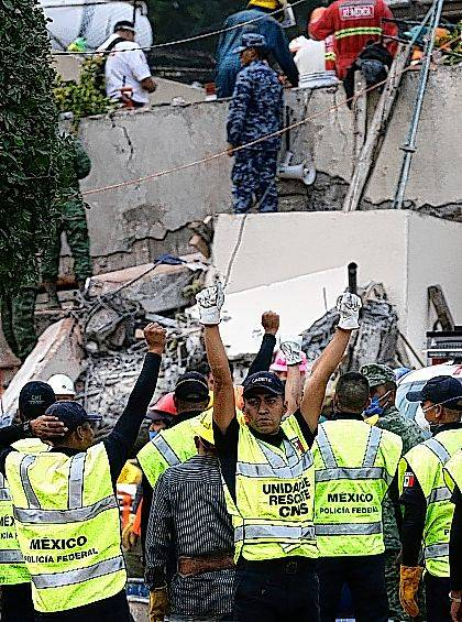 Rescue workers signal for silence during search and rescue efforts at the Enrique Rebsamen school that collapsed after an earthquake in Mexico City, Wednesday, Sept. 20, 2017. Police, firefighters and ordinary Mexicans dug frantically through the rubble of collapsed schools, homes and apartment buildings early Wednesday, looking for survivors of Mexico's deadliest earthquake in decades as the number of confirmed fatalities climbs. One of the most desperate rescue efforts was at this school, where a wing of the three-story building collapsed into a massive pancake of concrete slabs. (AP Photo/Marco Ugarte)