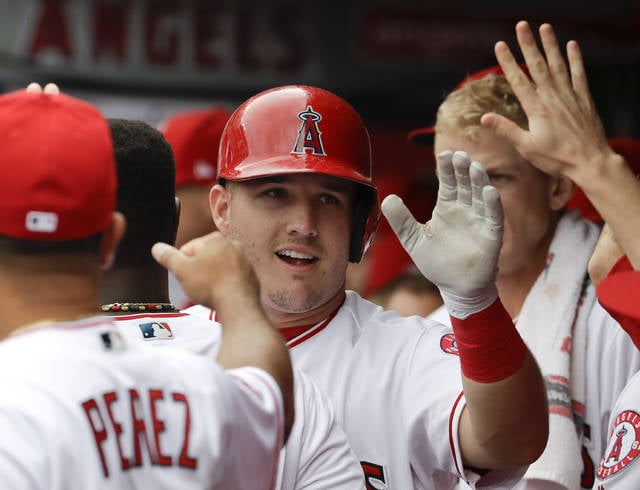 Los Angeles Angels' Mike Trout celebrates in the dugout after scoring on a double by Albert Pujols during the first inning of a baseball game against the Cleveland Indians in Anaheim, Calif., Thursday, Sept. 21, 2017. (AP Photo/Chris Carlson)