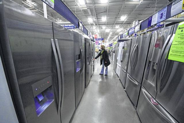 A woman walks through a display of refrigerators at a Lowe's store in Cranberry Township, Pa. Buying a major appliance can be intimidating, but it doesn't have to be hard. To find one that both you and your bank account are happy with, do your homework, visit a store and ask for a deal. And don't buy an extra warranty without reading the fine print.