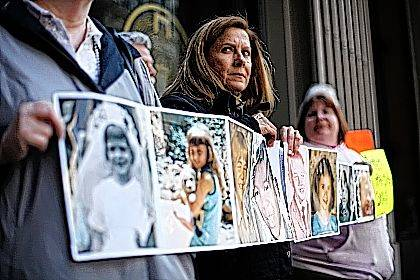 In this March 29, 2011, file photo, Barbara Blaine, president of Survivors Network of those Abused by Priests, displays childhood photographs of adults who say they were sexually abused, during a news conference in Philadelphia. Blaine, the founder and former president of the Survivors Network of those Abused by Priests, has died. The organization known as SNAP announced on its Facebook page that Blaine died Sunday following a recent cardiac event. She was 61.