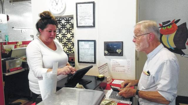 Michelle Lambert, left, takes former Lima City Councilman David Adams' order Friday at the Fat Cat Diner. Friday was the last day the diner would offer diner-style service, with the business transitioning to catering and delivery.