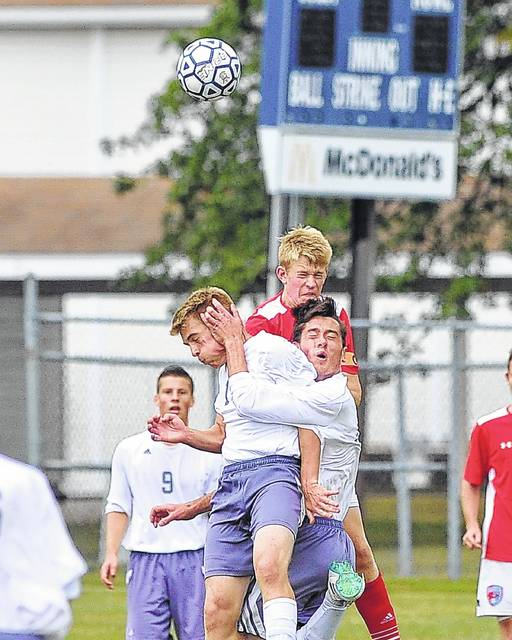 Temple Christian's Jonathan Acklin (left) and Ethan DeLeon (middle) and Lima Central Catholic's Ben Brinkman collide on a header during Thursday's match at Temple Christian.