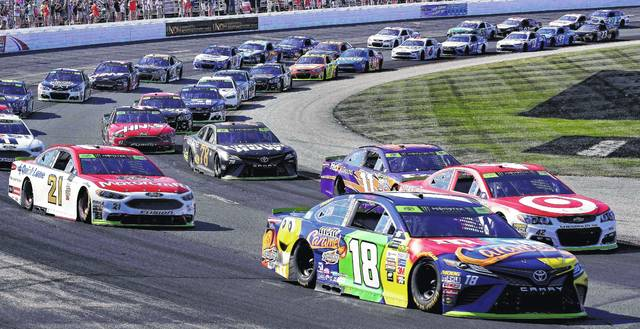 Kyle Busch (18) leads the pack into turn one in the first lap of the NASCAR Cup Series 300 auto race at New Hampshire Motor Speedway in Loudon, N.H., Sunday, Sept. 24, 2017. (AP Photo/Charles Krupa)