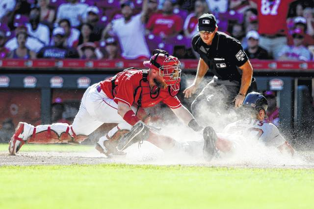 Boston Red Sox's Mookie Betts, right, scores the go-ahead run against Cincinnati Reds catcher Tucker Barnhart, left, in the eighth inning of a baseball game, Sunday, Sept. 24, 2017, in Cincinnati. The Red Sox won 5-4. (AP Photo/John Minchillo)