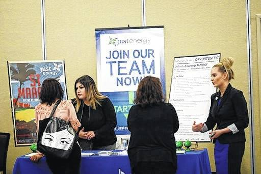Heather Snow, at right, and Daisy Medina, second from left, recruiters for Just Energy, talk to job seekers during an August job fair in San Jose, Calif. Changing careers takes energy, money and time. Before giving up the security of your current position, there are steps you can take to be sure you're making the right decision.