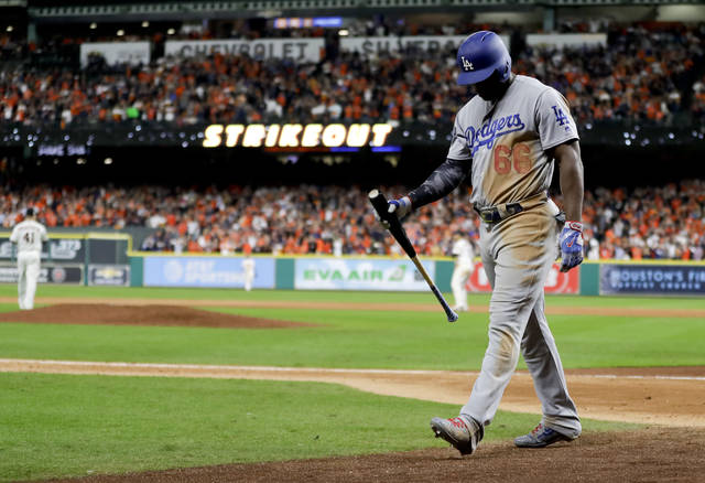 Los Angeles Dodgers' Yasiel Puig walks to the dugout after striking out against the Houston Astros during the ninth inning of Game 3 of baseball's World Series Friday, Oct. 27, 2017, in Houston. (AP Photo/Matt Slocum)