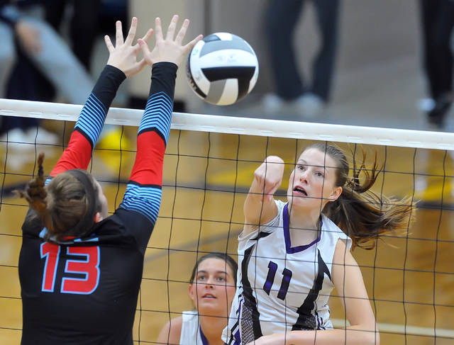 Ada's Megan Light hits a spike against Lima Central Catholic's Rosie Williams during Thursday's Division IV district final at the Ottawa-Glandorf High School.
