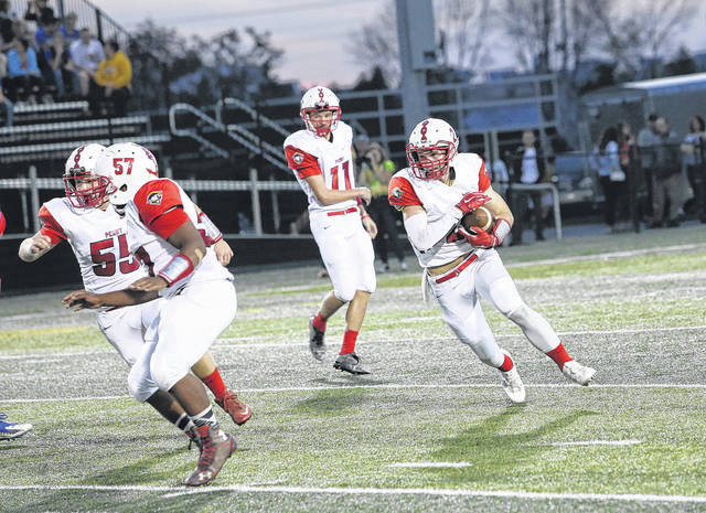 Perry's Aaron Rush (55) and Isaiah Davis (57) lead the way for running back Shane Overly during Friday night's game in Sidney.