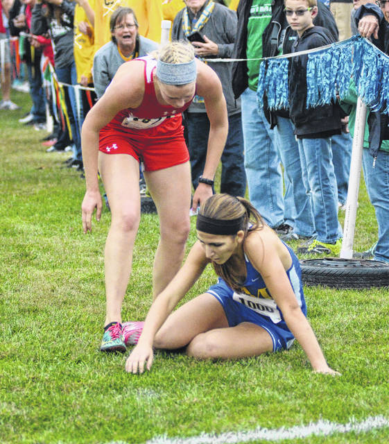 Wapakoneta's Michaelia Fisher stops short of the finish line to check on fallen St. Marys runner Laura Wilker during the Western Buckeye League girls high school race Saturday at Bath High School. Fisher finished 21st and Wilker finished 22nd.