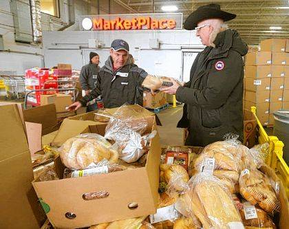 In this Nov. 16, 2017 photo, Erik Gunsberg, left, a member of Second Chance Village, gathers food with founder Sage Lewis at the Akron-Canton Regional Foodbank in Akron, Ohio. Since a railroad company ordered a homeless camp off the Cuyahoga Valley Scenic Railroad in January, the Second Chance Village has become a magnet for hundreds of homeless Akronites. (Phil Masturzo/Akron Beacon Journal via AP)