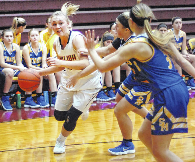 Kalida's Kara Siefker drives to the basket against St. Marys defenders Ally Will (3) and Clare Caywood during Tuesday night's game at Kalida.