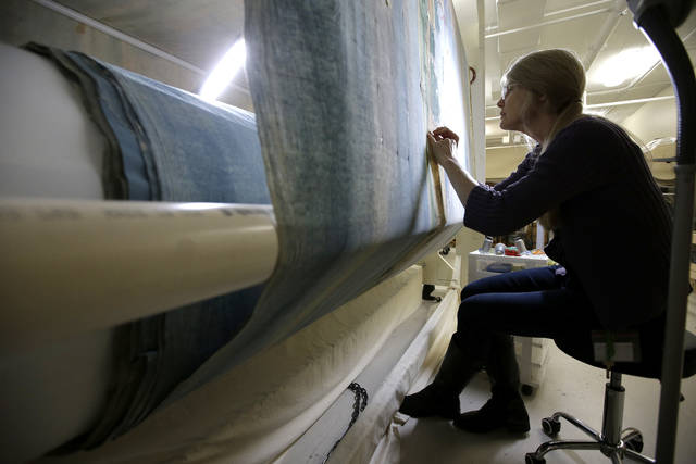 """Photo textile conservator Kate Tarleton, of Rochester, Mass., works Nov. 7 to restore a portion of the 1848 """"Grand Panorama of a Whaling Voyage Round the World,"""" at the New Bedford Whaling Museum, in New Bedford, Mass. The artifact is believed to be the longest painting in the world at about a quarter mile long."""