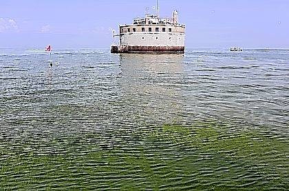 In this Aug. 3, 2014, file photo, the water intake crib for the city of Toledo is surrounded by an algae bloom on Lake Erie, about 2.5 miles off the shore of Curtice. Ohio's strategy for sharply reducing what's making algae flourish in Lake Erie clearly shows that changes in farming methods are what's needed. The blueprint also has a long list of ways to do that, researchers say, but it lacks a clear direction on what to do next.
