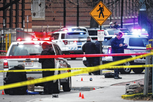 In this Nov. 28, 2016, file photo, crime scene investigators collect evidence from the pavement as police respond to an attack on the Ohio State University campus in Columbus. In a video released Monday before the anniversary of the attack, Ohio State University Police officer Alan Horujko credits his training for allowing him to quickly stop the man responsible, according to a video released Monday. Horujko shot and killed Abdul Razak Ali Artan after the 18-year-old drove into a crowd outside a classroom building and attacked people with a knife.
