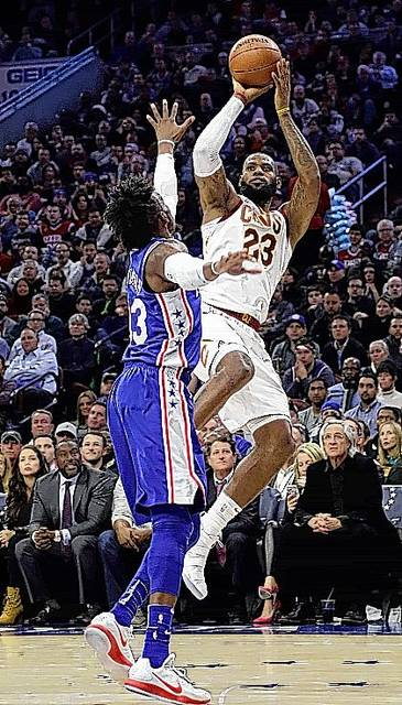 Cleveland Cavaliers' LeBron James, right, goes up for a shot against Philadelphia 76ers' Robert Covington during the first half of an NBA basketball game, Monday, Nov. 27, 2017, in Philadelphia. (AP Photo/Matt Slocum)