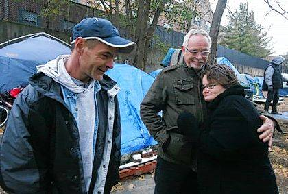In this Nov. 10, 2017 photo, Eric Gunsberg, left, of Second Chance Village, talks with Gary Beasley, of Indianapolis, center, and his daughter Stephanie Beasley, a former resident of the village, during a tour of the tent city homeless village in Akron, Ohio. Stephanie's family saw her on a video about Second Chance Village and traveled to Akron to find her. (Mike Cardew/Beacon Journal/Ohio.com via AP)