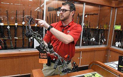 Steve Cope, store manager at Big R Store in Lima, explains some of the features on a Bear compound bow while in the sporting goods department on Thursday. The Bear, Marshall RTH style compound bow sales for $499.