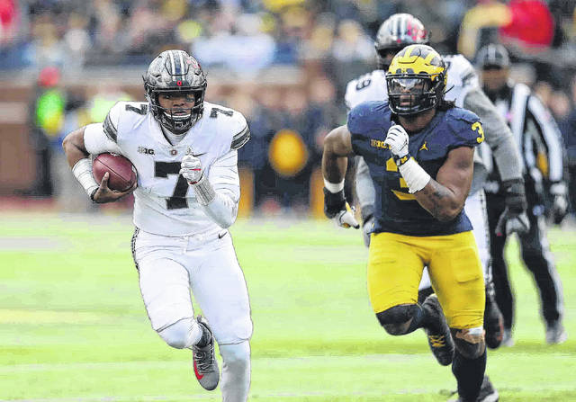 Ohio State quarterback Dwayne Haskins gains yards as Michigan's Rashan Gary gives chase during Saturday's game at Michigan Stadium in Ann Arbor, Mich. See more game photos at LimaScores.com