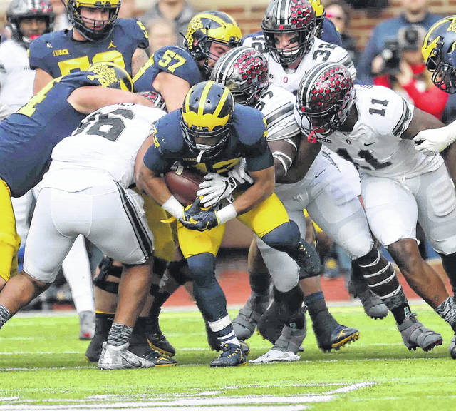 Ohio State's Dre'Mont Jones, left, Robert Landers, middle, and Jalyn Holmes (11) halt Michigan's Austin Mack during Saturday's game at Michigan Stadium in Ann Arbor, Mich.