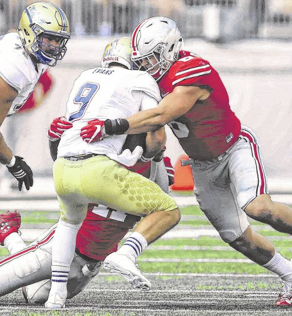 Ohio State Jalyn Holmes (11) and Ohio State Sam Hubbard (8) combine to wrap up Tulsa quarterback Dane Evans for a first quarter sack at Ohio Stadium in 2016.