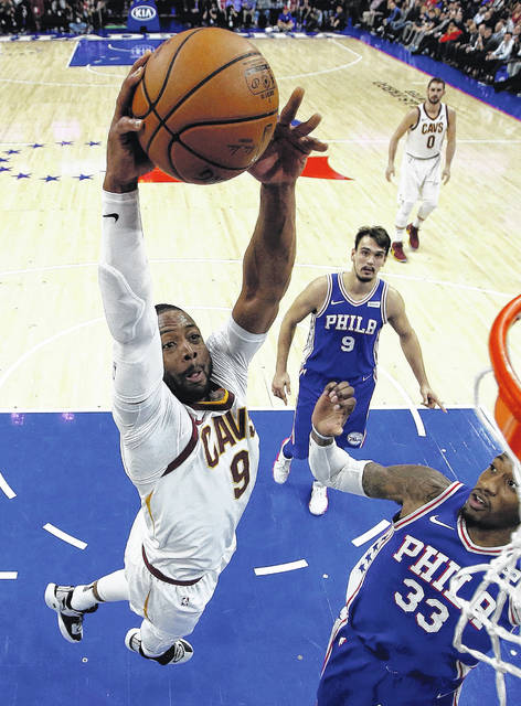 Cleveland Cavaliers' Dwyane Wade (9) goes up for a dunk past Philadelphia 76ers' Robert Covington (33) during the second half of an NBA basketball game, Monday, Nov. 27, 2017, in Philadelphia. Cleveland won 113-91. (AP Photo/Matt Slocum)