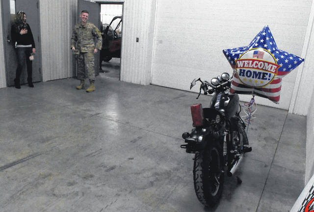 Steven Richards, right, of the Army National Grard, reacts to his newly rebuilt 1981 Yamaha SX650 during a family surprise event at Ohio Cycleworx in Lima. To the far left is his wife, Kelsey.