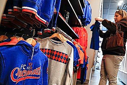 In this Wednesday, Nov. 29, 2017 photo,  Lisa Everson, of Fairfield, Ohio, shops for her children at the FC Cincinnati Team Store, Wednesday, Nov. 29, 2017, in Cincinnati. While Ohio's capital city is trying to figure out how to keep its Major League Soccer franchise, the Columbus Crew, from moving to Austin, Texas, folks in Cincinnati are working on getting one, by getting an expansion promotion for the FC Cincinnati team. (AP Photo/John Minchillo)