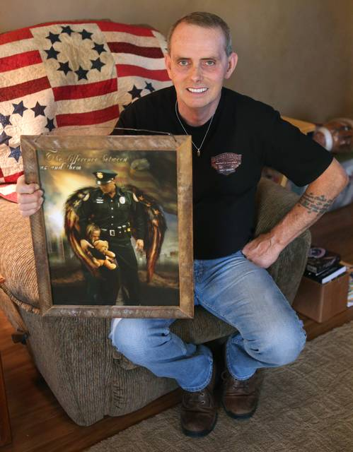 In this Dec. 20, 2017, photo, Uniontown police Sgt. David White poses for a photo with a gift presented to him by the Rittman Police Department, where is used to work, in Ohio. White said he is glad to be alive this Christmas. The officer in northeast Ohio's Union Township was shot four times after responding to a call about a man having fired a gun inside a home in July. (Scott Heckel/CantonRep.com via AP)