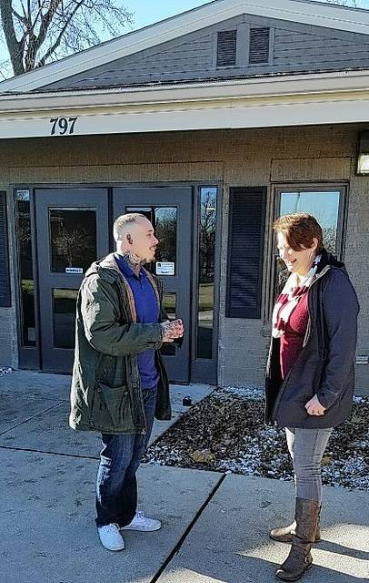 Coleman Professional Services recovery coaches Charlie Oen and Sara Hollar converse outside the Coleman building.