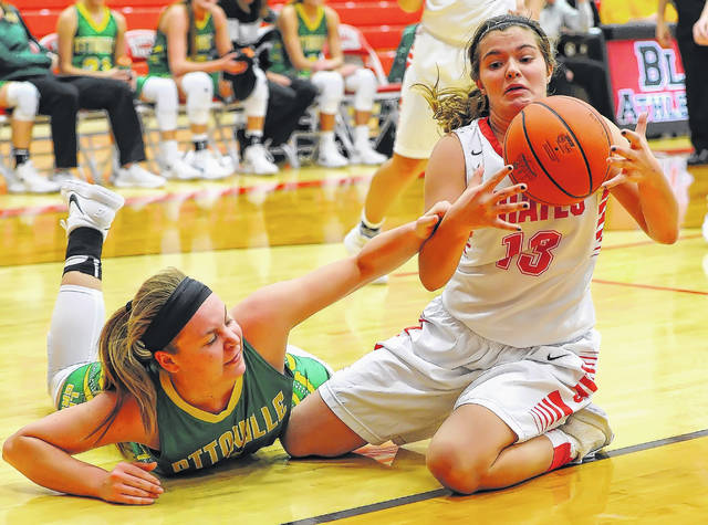 Ottoville's Brynlee Hanneman, left, reaches for a loose ball against Bluffton's Avery Rumer during Saturday's game at Bluffton High School.