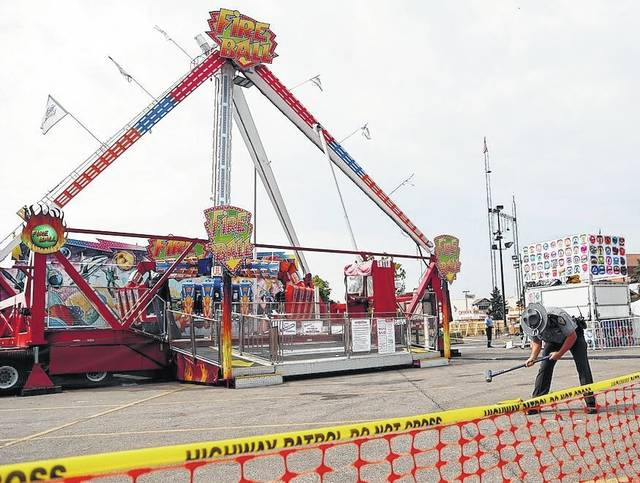 An Ohio State Highway Patrol trooper removes a ground spike from in front of the Fire Ball ride at the Ohio State Fair on July 27 in Columbus. Tyler Jarrell, 18, was killed and seven other people were injured when the thrill ride broke apart and flung people into the air.