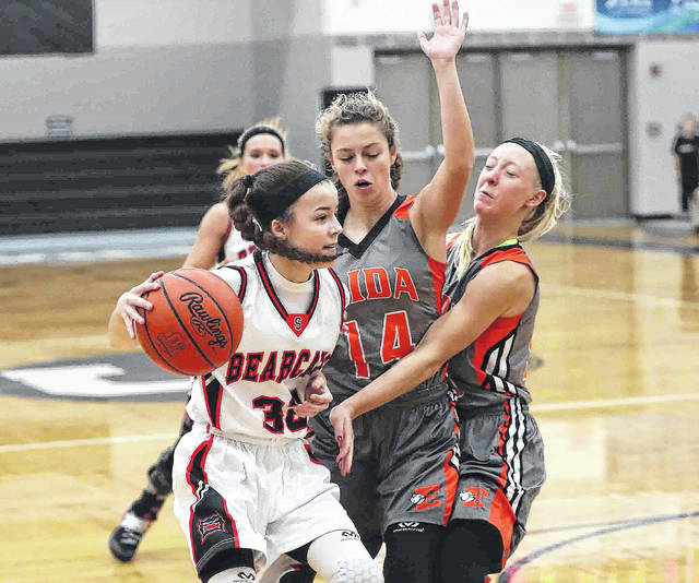 Elida's Erika Suever (14) and Hayleigh Bacome apply pressure to Spencerville's Abby Satterfield during Tuesday night's game at Spencerville High School. See more game photos at LimaScores.com.