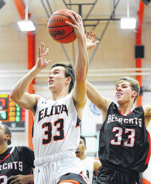 Elida's Daniel Unruh puts up a shot against Spencerville's Connor Holmes during Friday night's game at the Elida Fieldhouse.