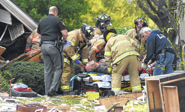 Firefighters place homeowner, Jim Mauk, on a gurney after being rescued from his home at 4230 Slabtown Road in Bath Township on Monday morning after the home exploded. Fran Mauk, his wife was also rescued from the home. Craig J. Orosz | The Lima News