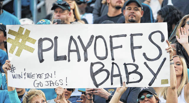 Fans hold up a sign as they cheer for the Jacksonville Jaguars during the second half of an NFL football game against the Houston Texans, Sunday, Dec. 17, 2017, in Jacksonville, Fla. (AP Photo/Stephen B. Morton)