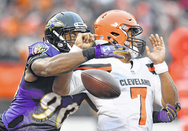 Baltimore Ravens defensive end Za'Darius Smith (90) knocks the ball loose from Cleveland Browns quarterback DeShone Kizer (7) during the second half of an NFL football game, Sunday, Dec. 17, 2017, in Cleveland. Ravens nose tackle Brandon Williams scored on a 1-yard fumble recovery. (AP Photo/David Richard)