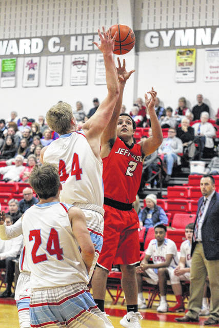 Delphos Jefferson's Brenen Auer attempts a shot against Lima Central Catholic's Mark Janowski during Friday night's game at LCC.