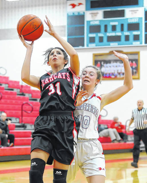 Spencerville's Nelaya Burden (31) goes to the hoop with Lima Central Catholic's Sophia Santaguida (10) defending during Monday's game at Msgr. Edward C. Herr Gymnasium.