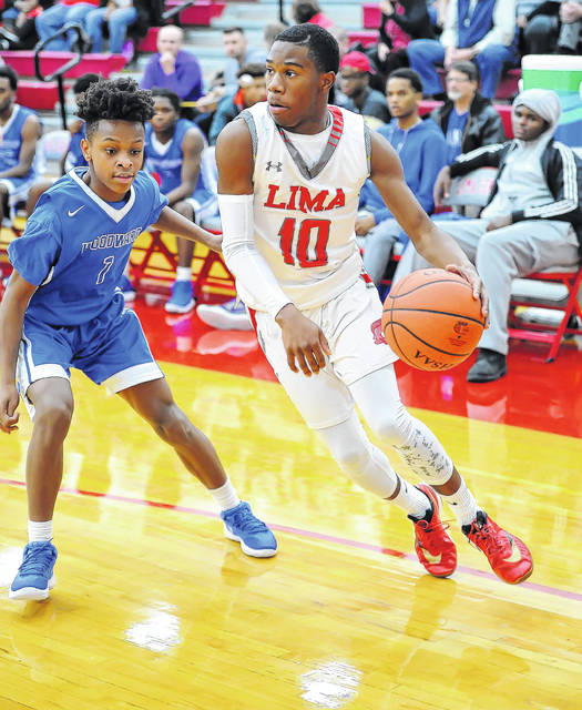 Lima Senior's Amihr Curtis drives against Woodward's Delveon Lear during Friday night's Kewpee Holiday Classic at Lima Senior High.